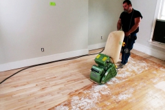 A man uses a large sander to sand the floors in an older home that is being renovated.